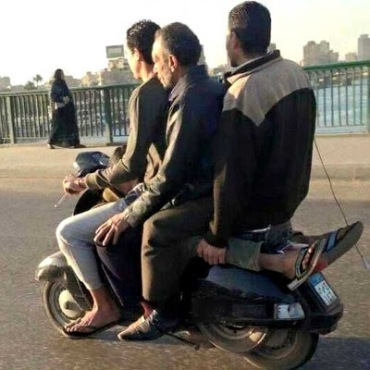 Four men on a scooter